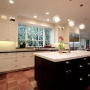 Contrasting cabinetry finishes and countertops add interest, create dynamic tension